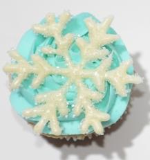 Cupcake à la vanille recouvert de glaçage au beurre bleu et décoré avec un flocon de neige fait de chocolat blanc