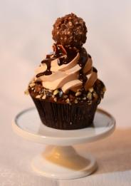 Cupcake au chocolat recouvert d'une fine couche de ganache au chocolat et de noisettes grillées. Tourbillon de crème meringue au beurre, ganache au chocolat et un Ferrero Rocher