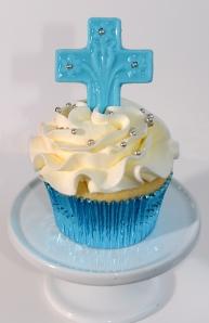 Cupcake à la vanille recouvert de glaçage meringue suisse au beurre. Croix bleue en chocolat sur le dessus.