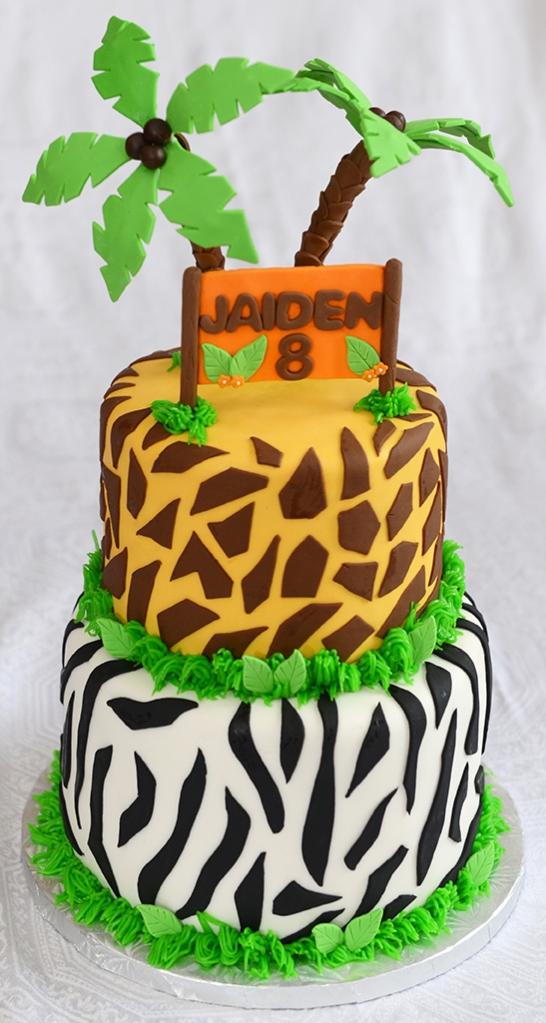 Gâteau deux étages. Le bas à motif de zèbre à l'extérieur et à l'intérieur (8 pouces). Le haut à motif de girafe à l'intérieur et à l'extérieur (6 pouces). Glaçage à la vanille meringue suisse. Décoré avec des palmier et une affiche en pastillage. - 85$