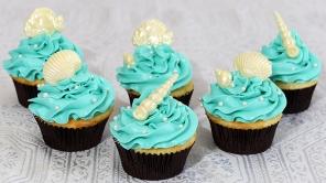 Cupcakes à la vanille recouvert de glaçage meringue suisse au beurre. Décoré avec un coquillage en chocolat et des perles de bonbon.