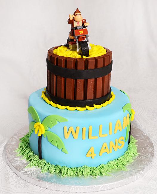 Gâteau Donkey Kong 2 étages à la vanille. 1er étage : 8 pouces recouvert de fondant et de décorations en fondant. 1er étage: 4 pouces recouvert de chocolat Kit Kat et de bananes en bonbon.