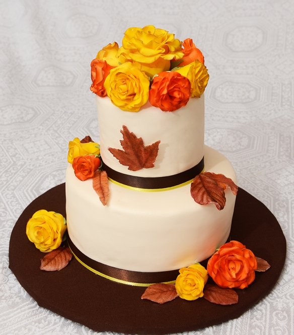Gâteau 2 étages (4 pouces et 7 pouces) aux épices avec crème au beurre à la cannelle.  Décoré avec les roses en sucre et des feuilles en chocolat.