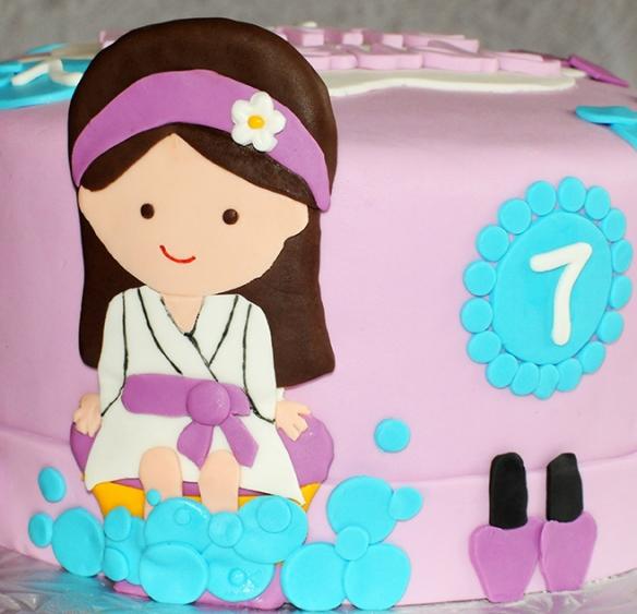 Gâteau 8 pouces à la vanille recouvert de fondant et décoré avec une fillette en fondant, des bulles et des bouteilles de vernis à ongle.