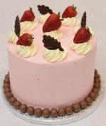 Gâteau au chocolat (4 étages) recouvert de crème au beurre meringue suisse aux fraises. Décoré de fraises et feuilles en chocolat