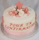Gâteau à la vanille avec crème au beurre meringue suisse aux fraises et recouvert de fondant. Croix en chocolat aux fraises et fleurs en pastillage.