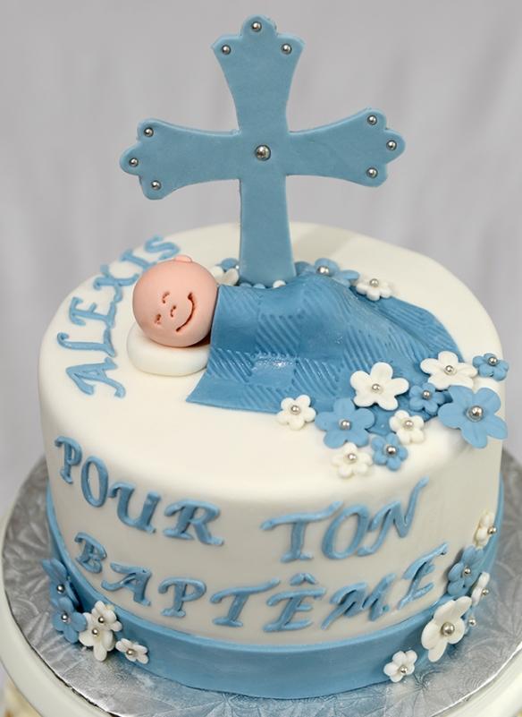 Gâteau 6 pouces à la vanille avec glaçage meringue suisse à la vanille recouvert de fondant et décoré d'une croix, bébé et fleurs en fondant.