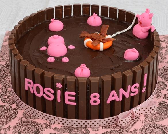 Gâteau 10 pouces au chocolat avec glaçage meringue Suisse au chocolat et ganache au chocolat. Contour en barre de chocolat kit kat. Cochons roses, lettres et autres objets en fondant.