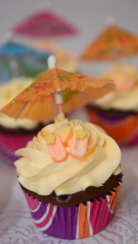 Cupcake au chocolat avec glaçage meringue Suisse à la vanille. Décoré avec parasol et flip flop en bonbon.