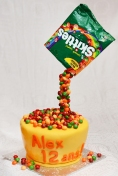 Gâteau 8 pouce à la vanille en forme de bol recouvert de fondant et rempli de skittles. Sac de skittles suspendu.