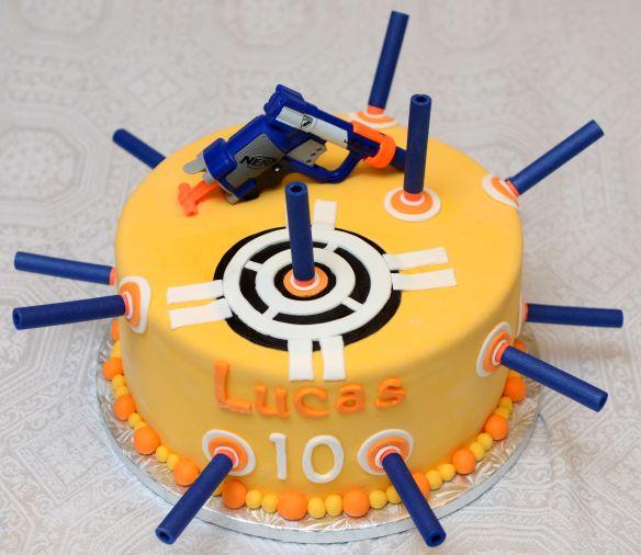 Gâteau 10 pouces au chocolat, glaçage meringue Suisse à la vanille et recouvert de fondant. Fusil nerf et flèches en plastique.