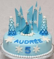 Gâteau de la reine des neiges 10 pouces à la vanille de couleur bleu. Recouvert de fondant et decorations faites en pastillage.