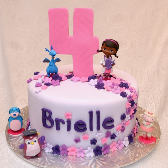 Gâteau 8 pouces à la vanille rose et mauve avec glaçage meringue suisse à la vanille et recouvert de fondant. Fleurs et chiffre 4 en pastillage, personnages en plastique.